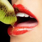 Sexy lips eating kiwi — Stock Photo