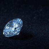 Blue diamond on black background with reflection — Stock Photo