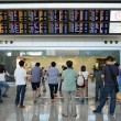 Hong Kong, China - September 14, 2013: Passengers looking at the large arrival board at Hong Kong Airport — Stock Photo