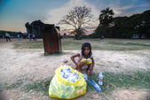 """""""Siem Reap, Cambodia - March 30, 2013 : A homeless Cambodian girl helps support her family by scavenging for empty bottles items that have been discarded on the angkor wat temple."""" — Stock Photo"""