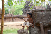 A boy sit on relaxed posture at Angkor wat Temple. (Leisurely boy) — Stock Photo