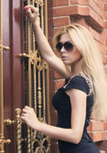 Girl in glasses and a black dress on the street — Stock Photo
