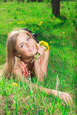 Beautiful girl with daisies lying on the grass — Stock Photo