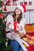 A beautiful young girl in a cap Santa Claus stretches gift — Stock Photo