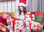 A beautiful young girl in a cap Santa Claus near gifts — Stock Photo