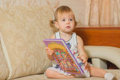 A little girl holding a book sitting — Foto de Stock