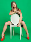 Beautiful girl in a black dress, sitting on a chair — Stock Photo