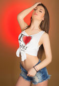 Beautiful girl teenager in denim shorts and shirt  — Stockfoto