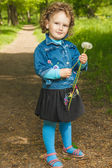 Little curly girl with dandelions  — Stock Photo