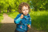 Little curly girl with soap bubbles  — Stock Photo