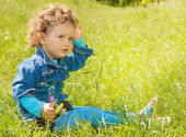 Little curly girl sitting on grass  — Stock Photo