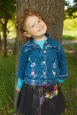 Little curly girl smiling in park — Stock Photo