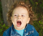 Little curly girl opens her mouth  — Stock Photo