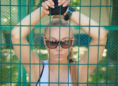 Beautiful athletic girl in sunglasses looking through the bars  — Stock Photo