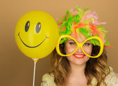 Cheerful girl in a bright wig and big glasses holding a balloon  — Stock fotografie