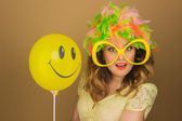 Beautiful girl in a bright wig and big glasses holding a balloon — Stock fotografie