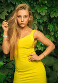 Beautiful athletic girl in a yellow dress posing on a background — Stockfoto