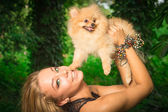 Beautiful smiling woman holding a small dog  — Stockfoto