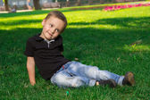 Little pensive boy sitting on the grass  — Stockfoto