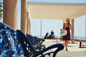 Blue bench at the sea and woman walking — Stock Photo