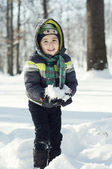 Portrait of funny child in winter playing with snow and laughing — Stockfoto