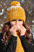 Woman sneezing into tissue, winter outdoor portrait — Stock Photo