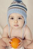 Bebê fofo sentado na cama e segurando uma laranja — Fotografia Stock