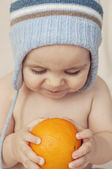 Cute baby sitting on the bed and watching an orange — Stock Photo
