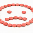 Red pills arranged in a sad smiley — Stock Photo