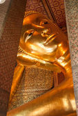 Reclining Buddha gold statue face. — Стоковое фото