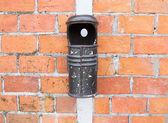 Oude bin en bakstenen muur — Stockfoto