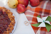 Pie and golden wedding rings on picnic — Stock Photo