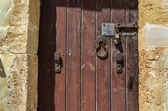 Old wooden door with rusty locks, latches and handles — Stock Photo