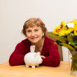 Stock Photo: Retiree with piggy bank