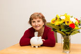 Retiree with a piggy bank — Stock Photo