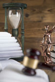 Wooden gavel, Lady Justice, gold scale and law books on wooden table — Stock Photo