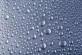 капли воды на серебряный серый фон — Стоковое фото