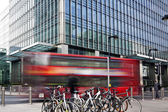 LONDON, UK - MARCH 10, 2014: Canary Wharf business aria. Public transport Famous Red Double Decker Bus and bikes bringing commuters to work — Stock Photo