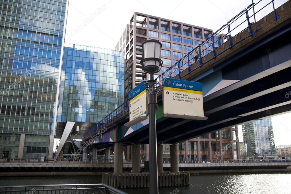 ONDON, CANARY WHARF UK - APRIL 13, 2014 - DLR bridge with train Modern glass architecture of Canary Wharf business aria, headquarters for banks, insurance, ...
