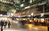 LONDON, CANARY WHARF UK - APRIL 4, 2014   Canary Wharf square view in night lights with office workers chilling out after working day in local cafes and pubs — Stock Photo