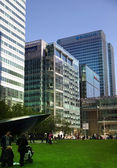 LONDON, CANARY WHARF UK - APRIL 13, 2014 - Modern glass architecture of Canary Wharf business aria, headquarters for banks, insurance, media and other world known companies Local park view — Stock Photo