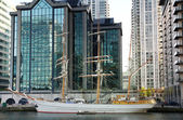 LONDON, CANARY WHARF UK - APRIL 4, 2014  Canary Wharf dock and antique yacht based against luxury apartments — Stock Photo