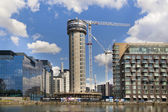 LONDON, UK - June 7, 2014: Building site with cranes in Canary Wharf aria. Raising new tallest residential tower in 43 floors in the business office aria — Stock Photo