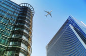 LONDON, UK - JUNE 30, 2014: Aircraft over the London's skyscrapers going to land in the City airport — Stock Photo