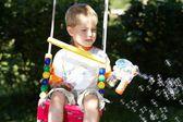 Niño jugando en los columpios con burbujas iridiscentes — Foto de Stock