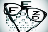 Medical eyeglasses on an eye chart — Stock Photo