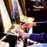 Постер, плакат: Men Playing with Slot Machines