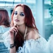The beautiful girl with red hair in a white dress sits a back to — Stock Photo