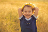 The beautiful little girl in a blue dress against a field laughs, holds hands behind the head — Stock Photo