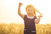 The beautiful little girl in a blue dress laughs, raising hands up — Stock Photo